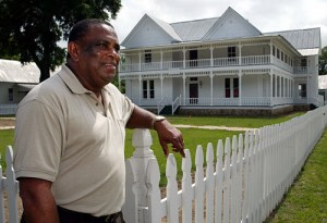 Toomsboro mayor Roger Smith stands at the fence of the newly restored bed and breakfast at the center of his mid-Georgia town